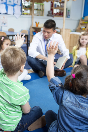 Male teacher giving a lesson to nursery students. They are sitting on the floor in a circle and some have their hands up to ask a question.
