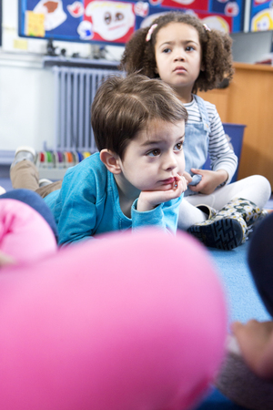 legs crossed on knee: Little boy lying on the floor at nursery during story time. Stock Photo