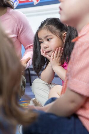 captivated: Little girl sitting with her legs crossed and her head in her hands during storytime at nursery.