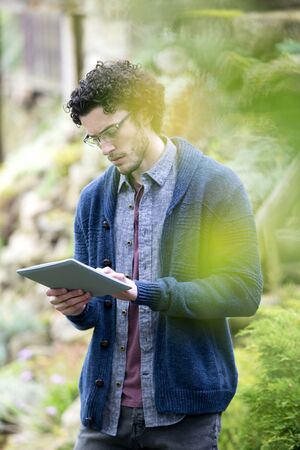 Young man using a digital tablet to analyse trees.