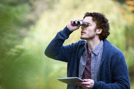 Jonge man analyseert de natuur met een verrekijker. Hij gebruikt een digitale tablet om te onderzoeken.