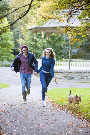 Young couple running through the park with their pet dog. Stock Photo