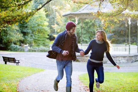 Young couple running togerther through a park in Autumn.