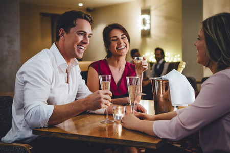 drinks after work: Group of friends enjoying a bottle of champagne in a restaurant.