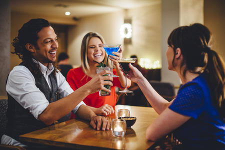 Groep vrienden roosteren cocktails in een restaurant. Stockfoto