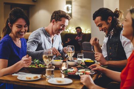 레스토랑에서 와인과 함께 저녁 식사를 즐기는 친구의 그룹입니다.