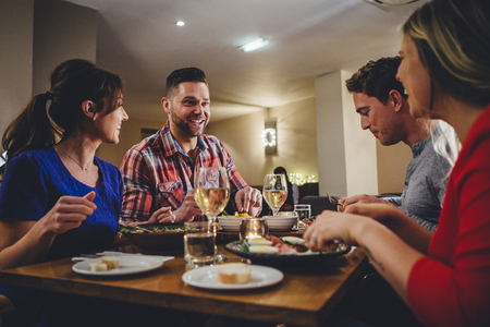 glasswear: Group of friends enjoying an evening meal with wine at a restaurant. Stock Photo