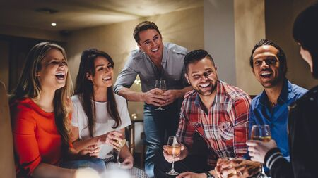 celebratory: Large group of friends enjoying a glass of wine together in a bar.