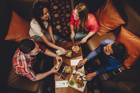 Bovenaanzicht van een groep van vrienden met een maaltijd in een restaurant. Ze eten hamburgers en vis met patat. Stockfoto - 60243814
