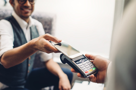 food technology: Business man making a contactless smartphone payment. Stock Photo