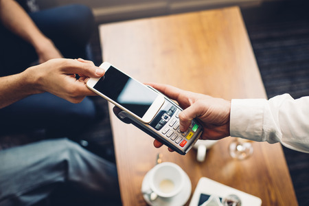 drinks after work: Business man making a contactless smartphone payment. Stock Photo