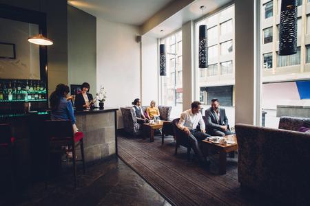 Volle zaal schot van een actieve bar en een café hotel. Er zijn mensen zitten en te drinken. Twee zakenmannen bespreken werk.