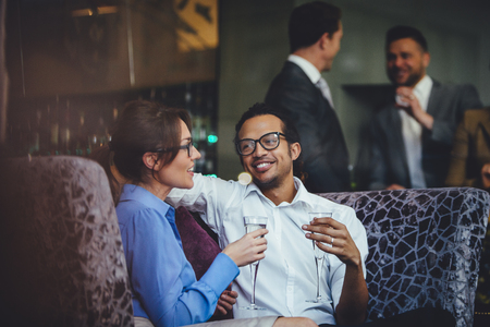 four person only: Couple enjoying a glass of champagne after work together at a bar.