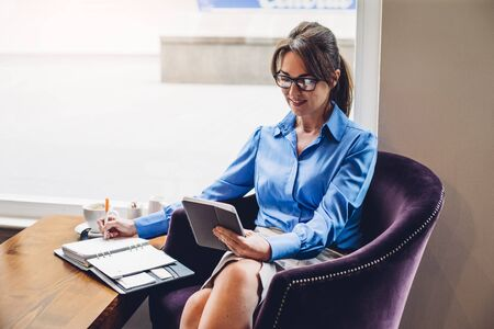 female legs: Mature business woman making notes and using a digital tablet in a cafe. Stock Photo