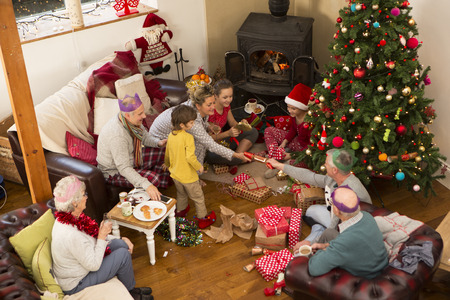 large tree: A family are sat around a christmas tree, opening presents and pulling crackers. Stock Photo
