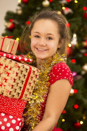A teenage girl is carrying a pile of Christmas presents, while smiling at the camera.