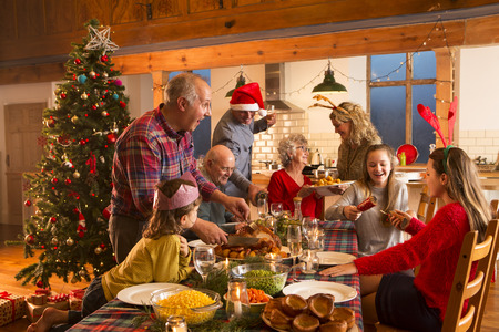 A large family are all helping serve Christmas dinner. Stock Photo