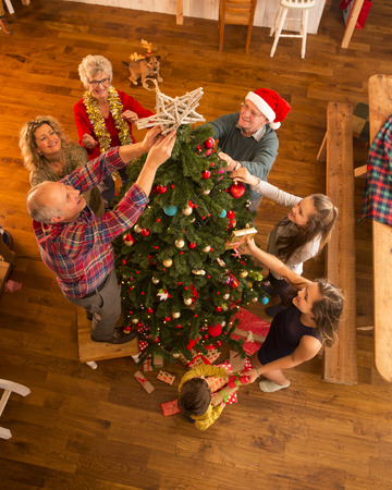 family tree: A large family are gathered around a christmas tree, adding decorations and putting presents under the tree. Stock Photo