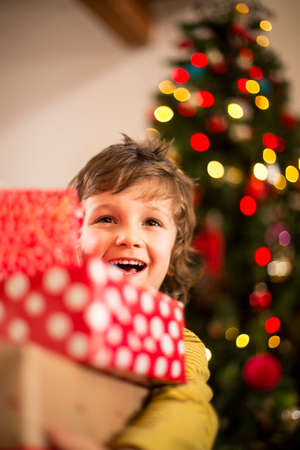 Little boy at Christmas holding all of his presents in front of the Christmas tree.