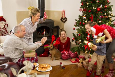 comida de navidad: Familia disfrutando de su mañana de Navidad. El padre está utilizando un teléfono inteligente para tomar una foto de dos de sus hijos. La madre y una de las hermanas están viendo. Foto de archivo