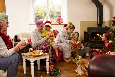 decoration messy: Family enjoying Christmas morning together. The children are opening presents with their parents and the grandmother is watching.