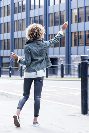 Young woman signalling for a taxi in the city centre. She is holding a smartphone with headphones and has her hand in the air.