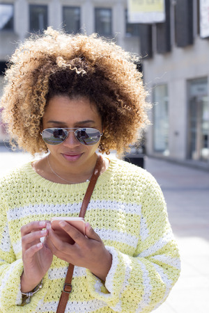 Woman in the city. She is wearing sunglasses and looking down to her smartphone which she is holding.