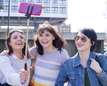 Three female friends taking a selfie in the city. They are using a smartphone on a selfie stick.