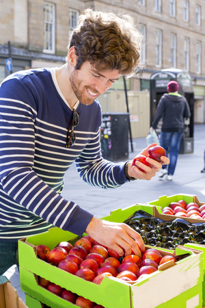 Young man in the city buying fresh fruit from a grocery market. Stock Photo