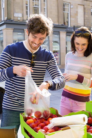 young couple buying fresh fruit from a grocery market.