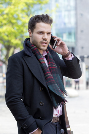 phonecall: Business man in the city. He is formally dressed and is talking to someone on his smartphone.