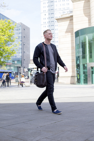 leather bag: Young man walking in the city. He has a leather bag and is dressed in casual clothing.