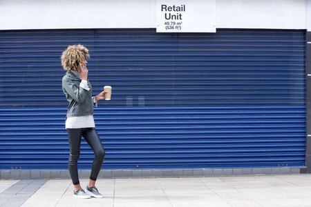 enquiring: Young woman enquiring about a retail unit on the phone. She is dressed casually and is holding a disposable coffee cup.