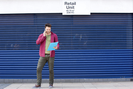 enquiring: Young man enquiring about a retail unit on the phone. He is dressed casually and is holding a clipboard. Stock Photo