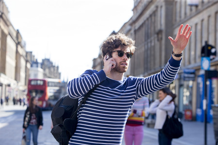 Busy man in the city. He is on the phone and has his hand out to signal for a taxi.