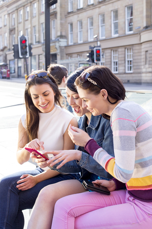 three women: three women in the city. They are sitting on a bench, looking at smart phones.