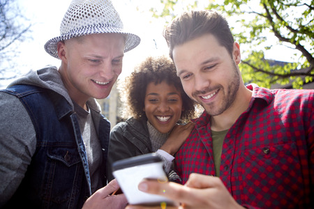 three friends: Three friends looking at a smart phone together outdoors.