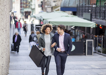 Couple in the city. They are walking arm in arm and the woman is holding a shopping bag. Reklamní fotografie