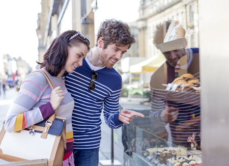 sweet treats: Young couple admiring sweet treats through the window of a bakery. Stock Photo