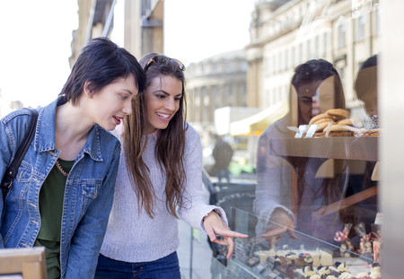 sweet treats: Two young women admiring sweet treats through the window of a bakery.