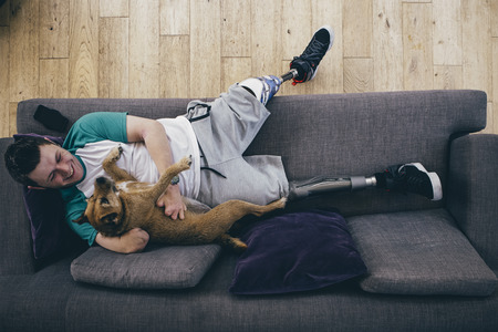 limbless: Quadruple amputee relaxing on the sofa at home with his dog.