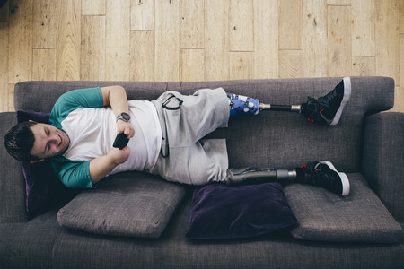 limbless: Quadriplegic man lying on the sofa at home. He is using a smartphone.