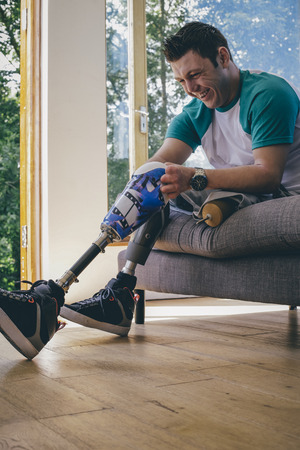 limbless: quadriplegic amputee putting his artificial legs on at home.