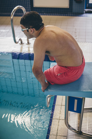 limbless: Quadriplegic swimmer ready to dive in. He is sitting on the platform with goggles on.