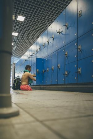 limbless: Quadriplegic athlete getting his belongings from the swimming locker.