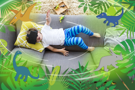 directly above: View from above of a little boy lying on his sofa with a box of dinosaurs. He is wearing a VR head set and there are dinosaur graphics around him.