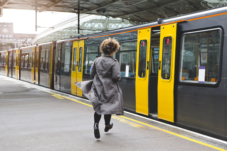 그것이 그녀없이 역을 떠나기 전에 기차를 타기 위해 실행하는 여자의 후면보기.
