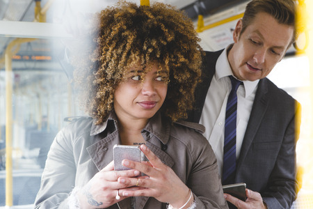 Man looking over a womans shoulder on the train at her phone screen. Stock Photo