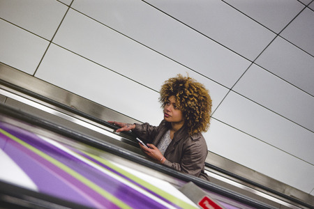 Woman travelling up an escalator from the subway train platform. She is holding a smart phone. Stock Photo
