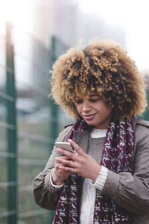 warm clothing: Woman using a smartphone outdoors. It is foggy and she is wearing warm clothing. Stock Photo